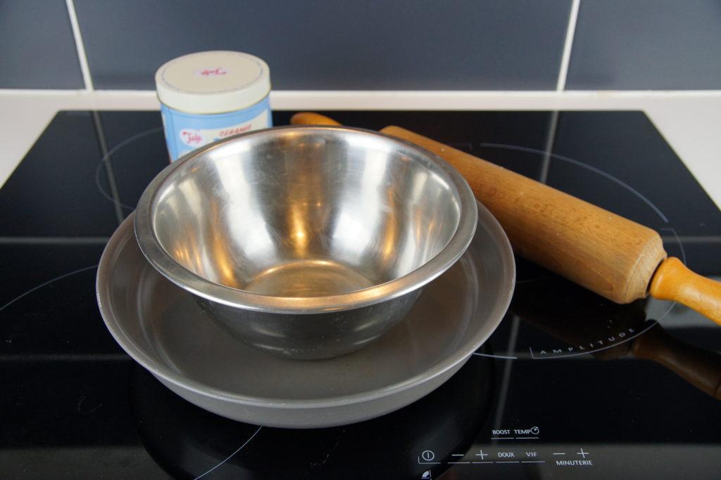 Pour faire une pâte brisée il faut un bol, un rouleau à patisserie, un plat à tarte et des billes en céramique