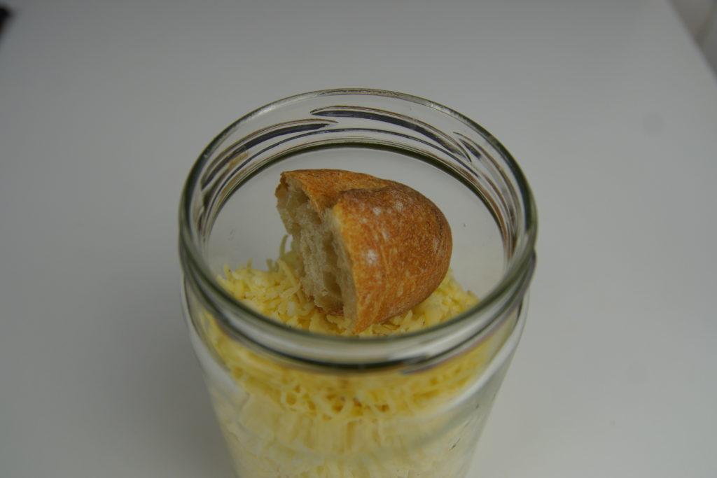 Crouton de pain dans le bocal de fromage râpé