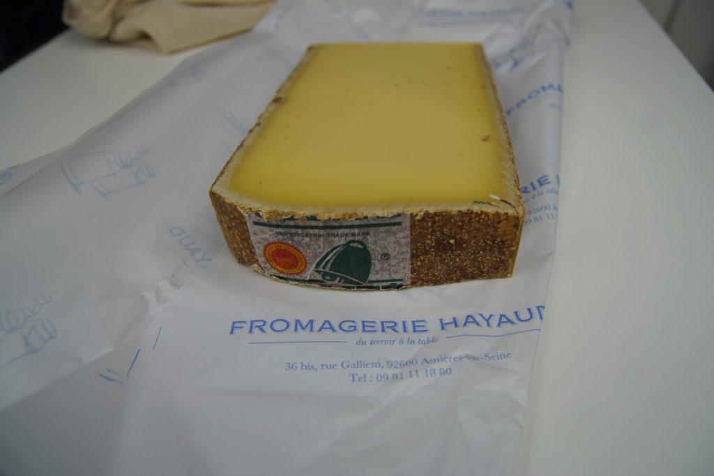 Morceau de Comté Bio posé sur l'emballage de la Fromagerie Hayaud à Asnières sur Seine
