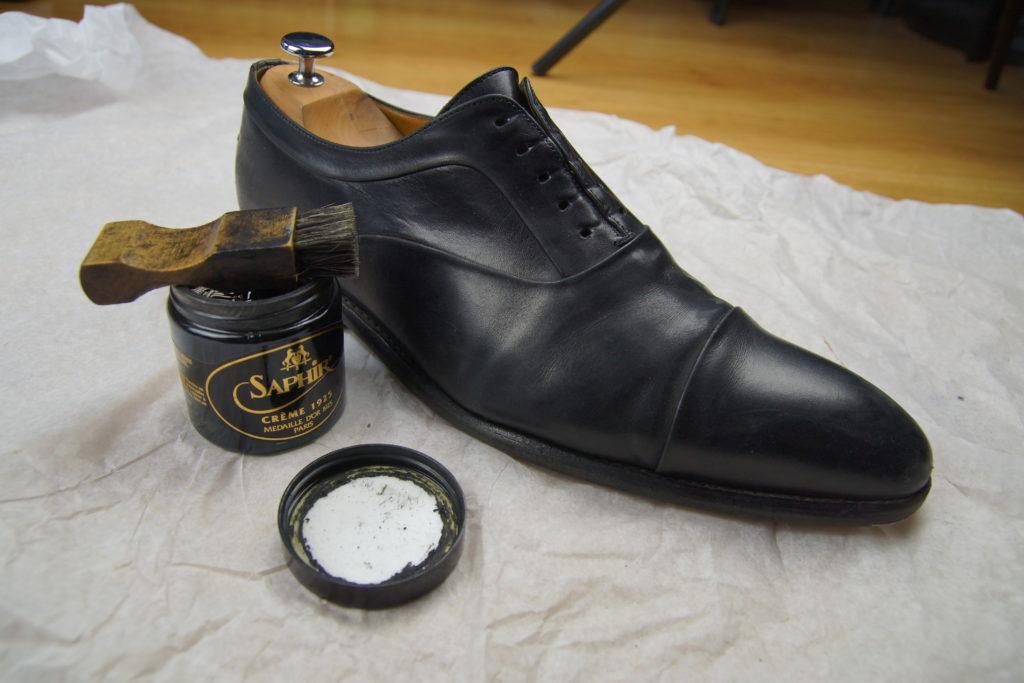 Palot posé sur un pot de crème de cirage à côté d'une chaussure à cirer