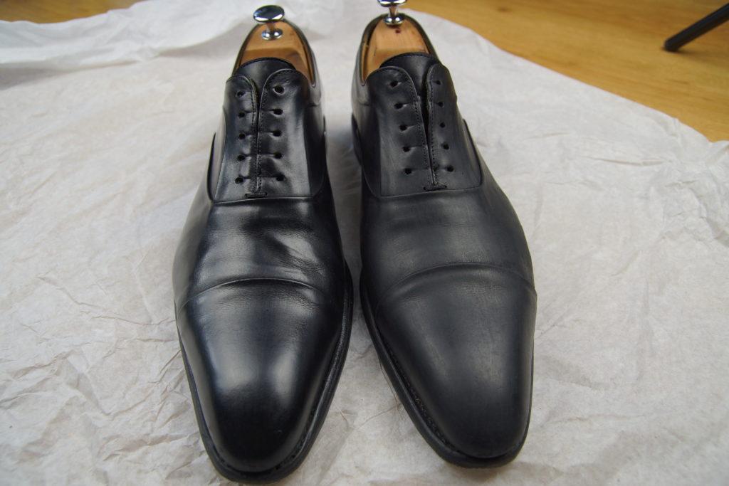 2 chaussures cirées sur le papier journal, celle de gauche frottée, celle de droite non