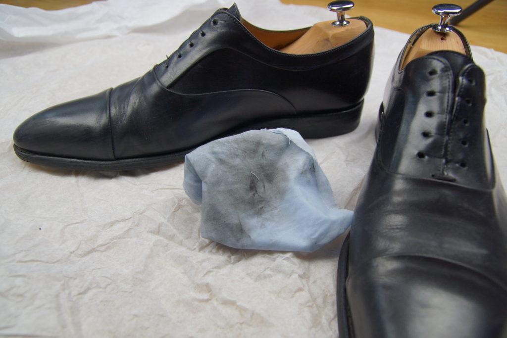 Chaussures nettoyées et le chiffon sale sur le papier journal